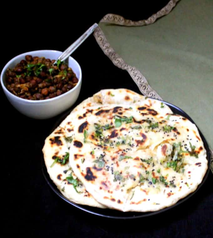 A frontal shot of three aloo kulcha in a black plate with pindi chole