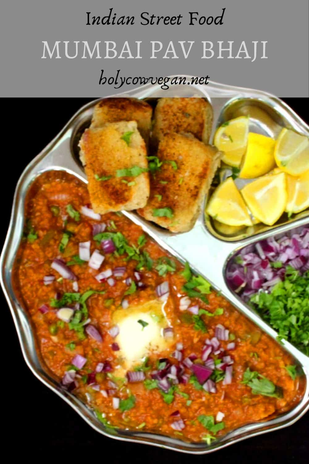 A plate of Pav Bhaji with butter, pao or pav bread rolls, lemons, onions and cilantro. A vegetarian vegan recipe from the streets of India,