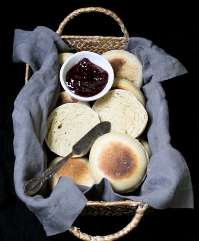 A wicker basket with a gray napkin and sourdough English muffins nestled inside with raspberry jam and a butter knife.