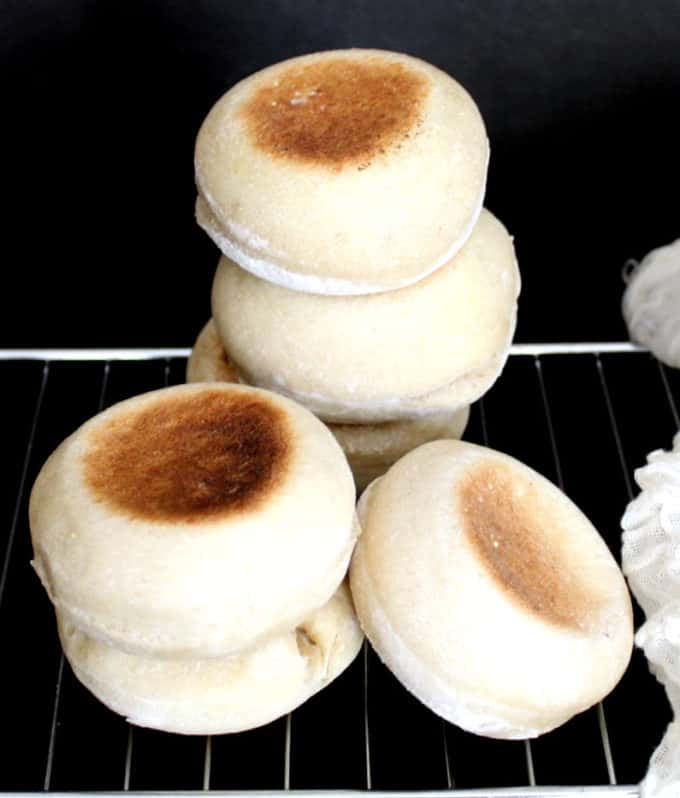 Stacks of Sourdough English Muffins perfectly baked cooling on a rack on a black background next to cheesecloth.