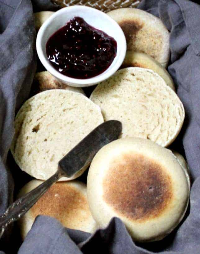A close up of sourdough English muffins in a wicker basket with gray napkin, raspberry jam and a butter knife