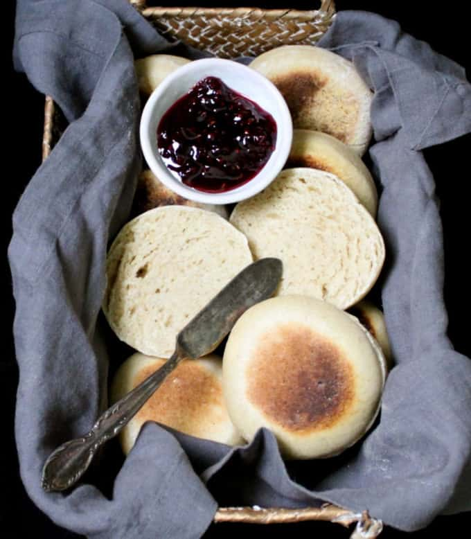 Close up of sourdough English Muffins in a wicker basket with a gray napkin and raspberry jam and a butter knife.
