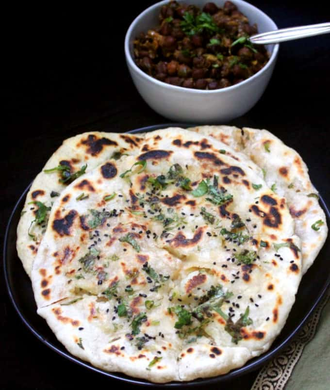 Aloo Kulcha piled on a plate with chana masala in a bowl