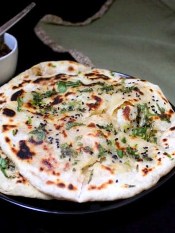 Stuffed Aloo Kulcha on a black plate witha green kitchen napkin and pindi chole