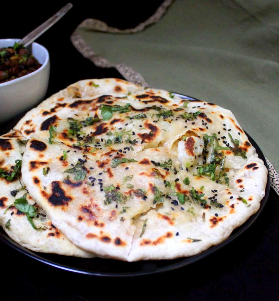 Stuffed Aloo Kulcha on a black plate witha  green kitchen napkin and pindi chole