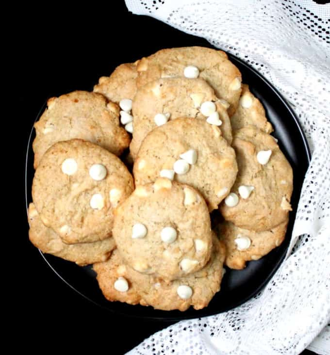 A top shot of a black plate with chocolate chip banana cookies with white chocolate and a white lace napkin