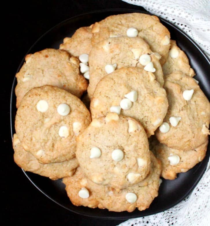 A close up top shot of  several vegan chocolate chip banana cookies with white chocolate chips in a black plate.