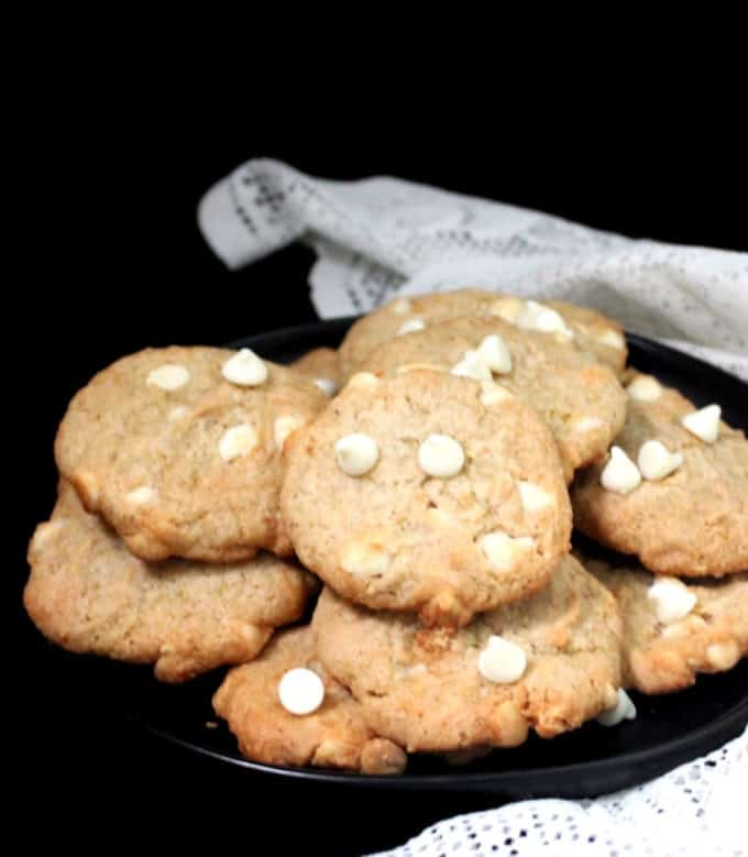 A front shot of several vegan white chocolate chip cookies on a black plate with a white lace napkin