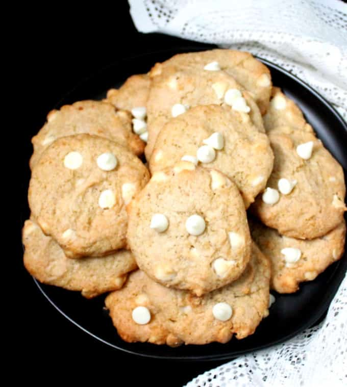 A front shot of vegan chocolate chip cookies on a black plate with a white napkin