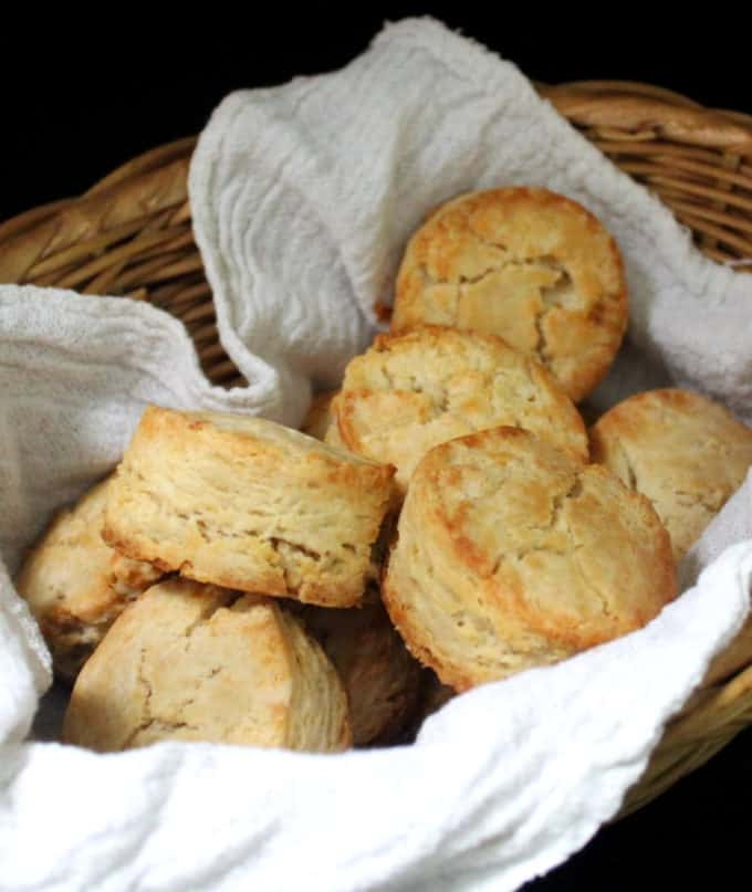 A close up of vegan sourdough biscuits nestled in a tea towel in a basket