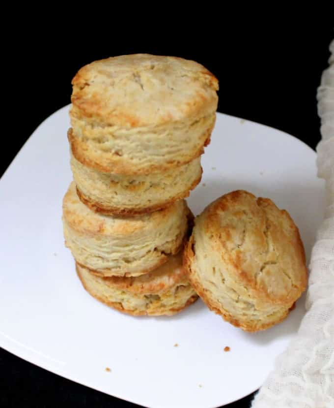 A stack of five flaky vegan sourdough biscuits on a white plate