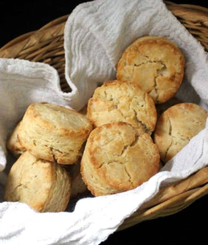 Close up shot of vegan sourdough biscuits nestled in a wicker basket with a flour sack napkin