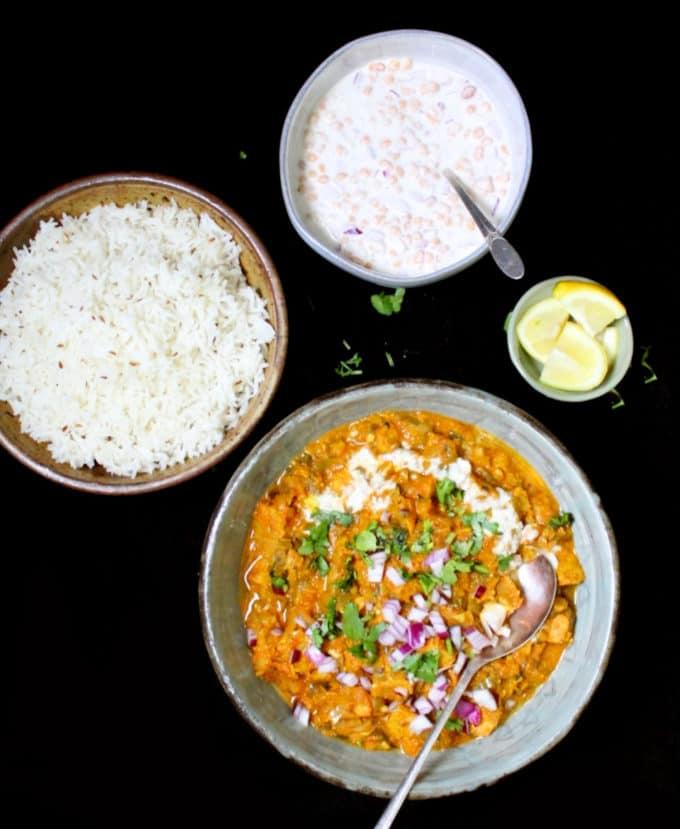 A distant overhead shot of vegan chicken masala with jeera pulao, lemon slices, cilantro, coconut cream and boondi raita.
