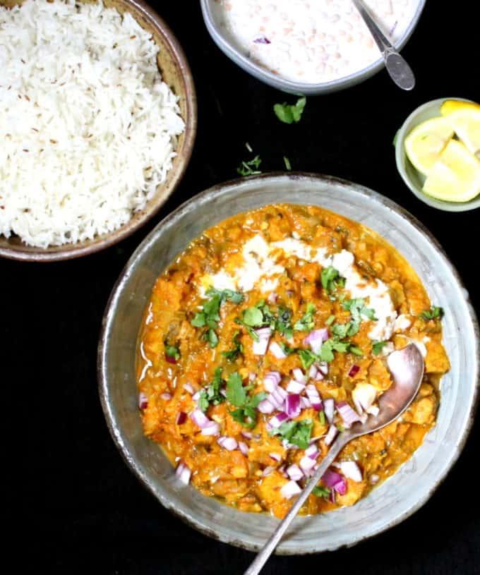 An overhead shot of vegan chicken masala with cilantro, cashew cream, jeera rice, boondi raita and lemons.