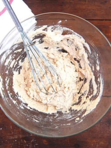 Sourdough starter made with flour and water in a bowl with a whisk and a kitchen napkin