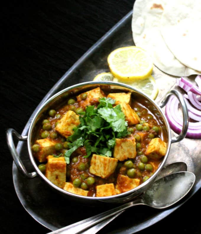 A front shot of matar paneer with tofu in a steel karahi bowl with lemon, roti, onions and two silver spoons.