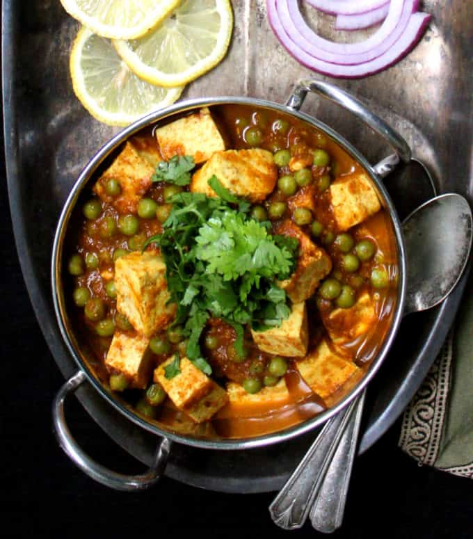 A kadhai bowl with mater paneer with cubes of tofu and green peas on a silver tray with wedges of lemon, roti and slices of onion.