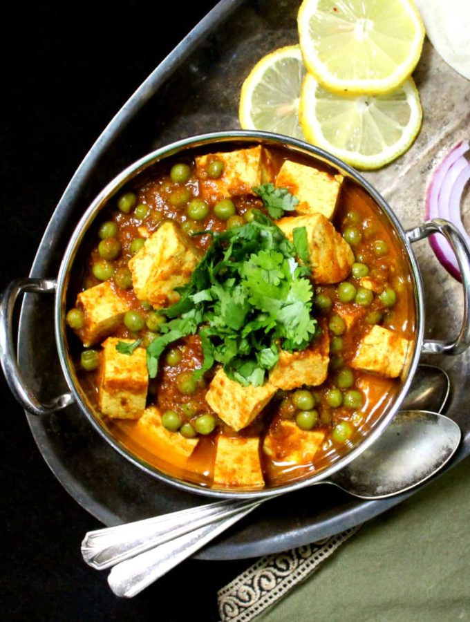 A kadhai serving bowl with matar paneer with tofu cubes in a tomato onion gravy sauce, with onions, lemons and roti