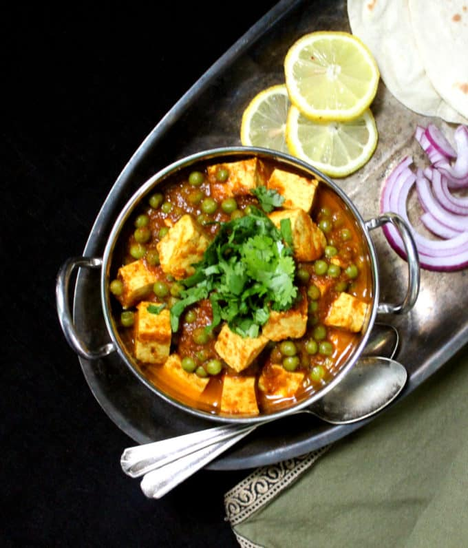 Overhead shot of matar paneer with lemon wedges, slices of onion, rotis and two spoons.