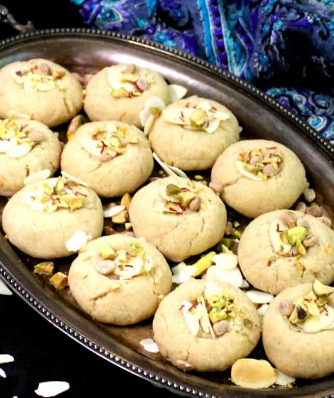 A close up shot of several vegan nankhatai biscuits on a silver plate with pistachios, almonds, saffron and other garnishes.