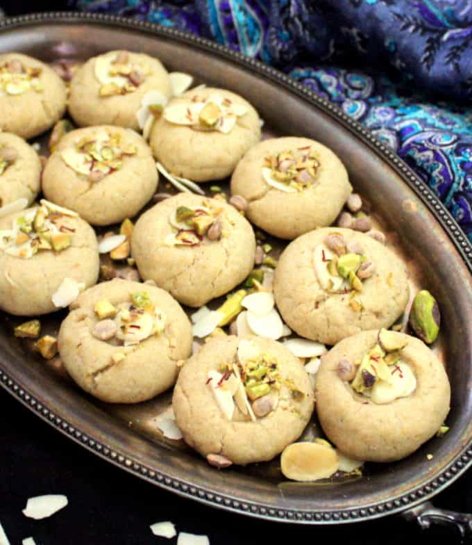 Close up of dairy-free vegan nankhatai studded with nuts on a black background.