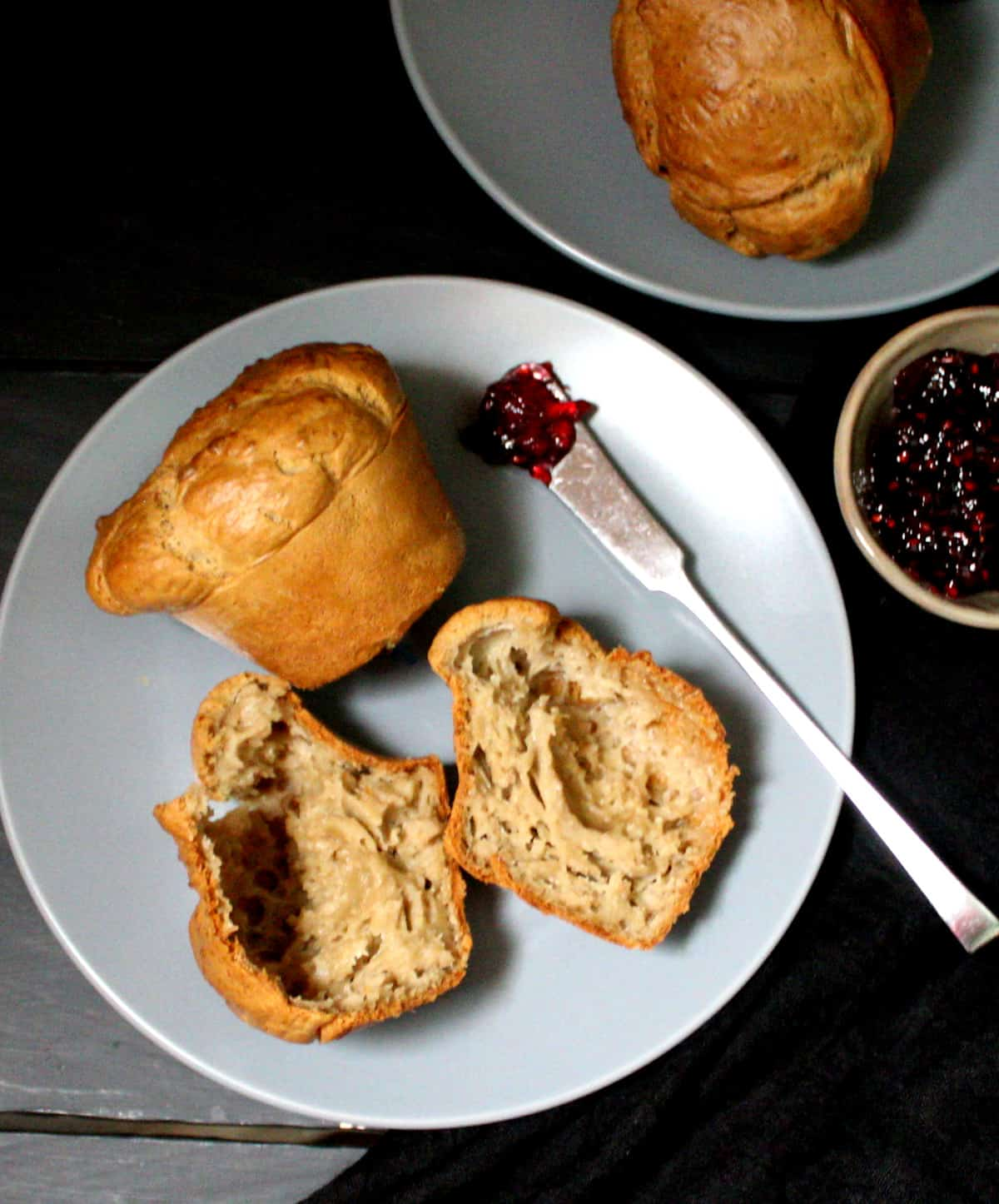 Overhead shot of vegan sourdough popovers on two gray plates with raspberry jam in a bowl and a butter knife.