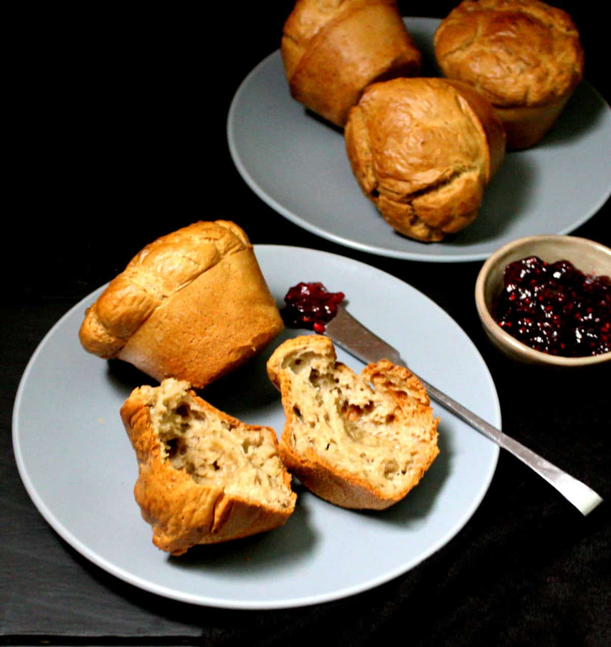 Front shot of plates of  vegan popovers with raspberry jam.