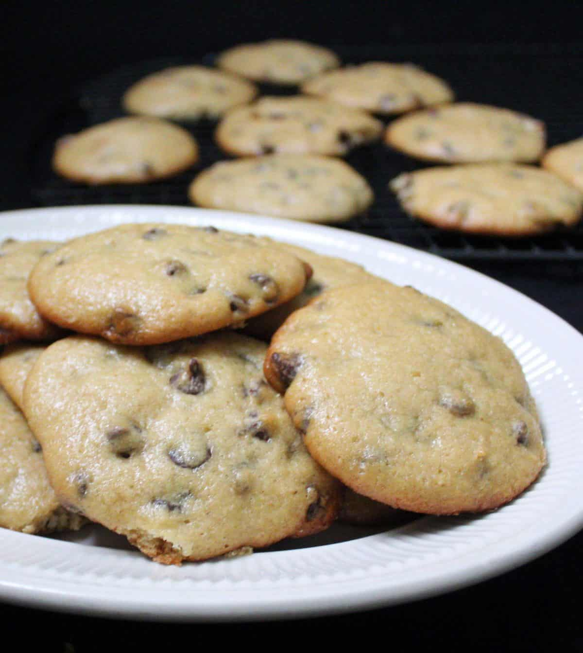 Close up of vegan sourdough chocolate chip cookies on a white plate.
