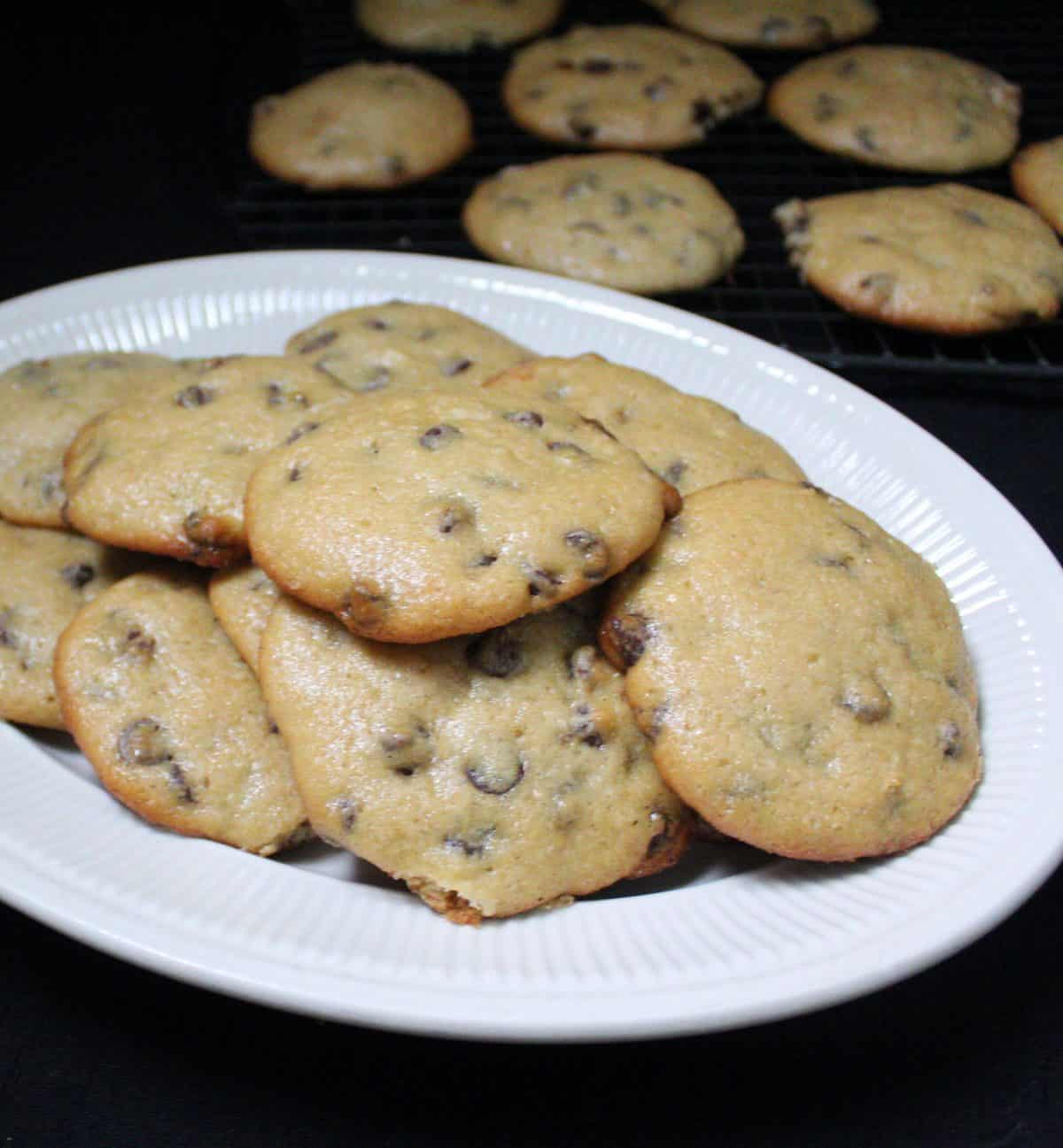 A front shot of a dish piled high with vegan sourdough chocolate chip cookies.