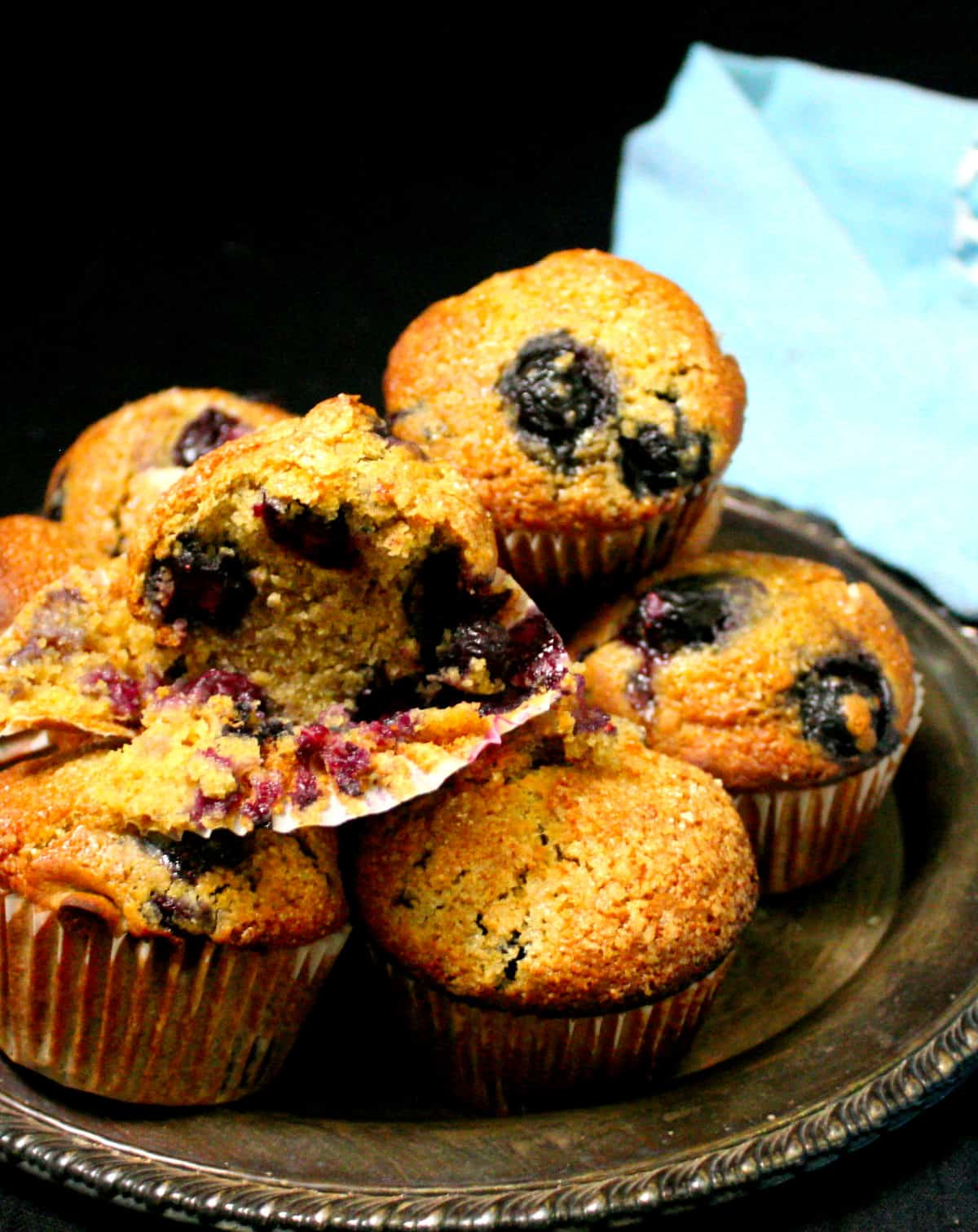 A front shot showing a partially eaten vegan blueberry sourdough muffin with others in a silver plate and a blue napkin.