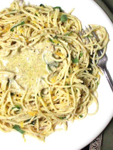 A close up of vegan lemon pasta with basil, lemon zest and a creamy olive-oil-lemon sauce