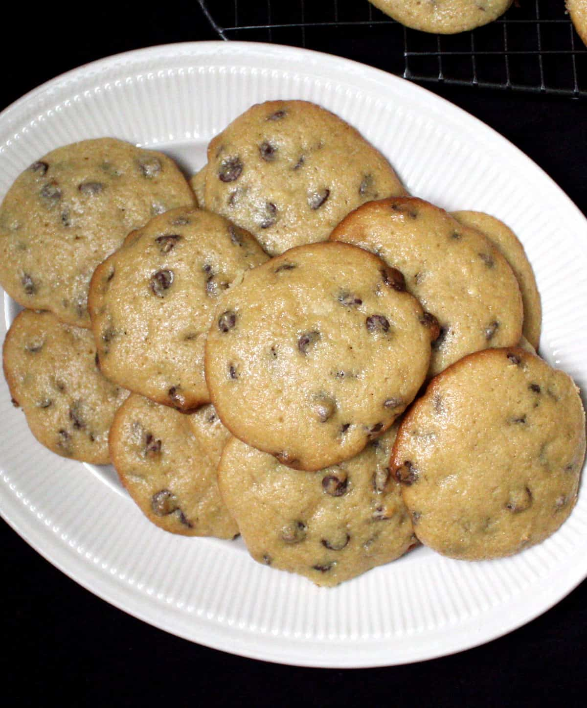 An overhead shot of vegan sourdough chocolate chip cookies on an oval white plate.