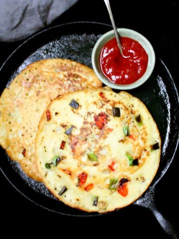Moonglet, a mung bean omelet packed with veggies, on a cast iron griddle with sauce on the side