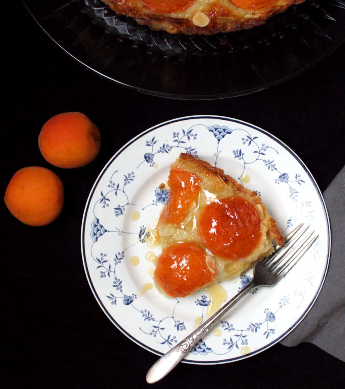 Overhead closeup of a vegan apricot frangipane tart with a silver fork.
