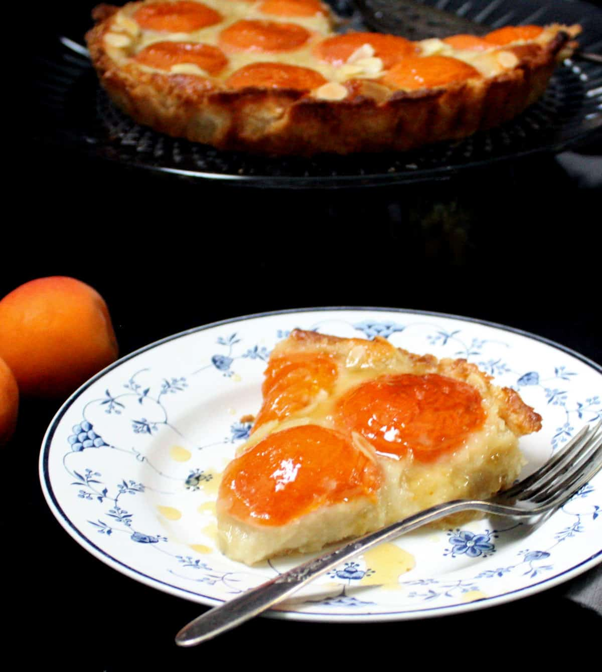 A plate with a slice of vegan apricot frangipane tart with a fork and fresh apricots.
