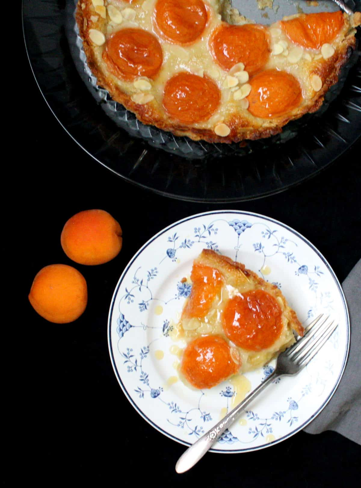 An overhead shot of a slice of vegan apricot frangipane tart with fresh apricot halves in a blue and white plate, standing next to the full tart on a glass stand.