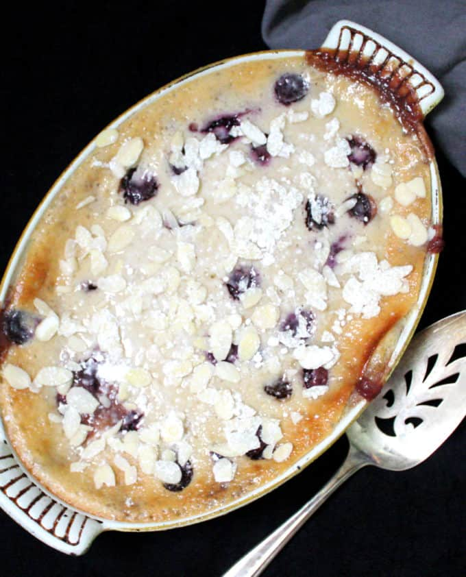 Close up overhead shot of a vegan cherry clafoutis dusted with powdered sugar and almonds with a pie server and a gray napkin