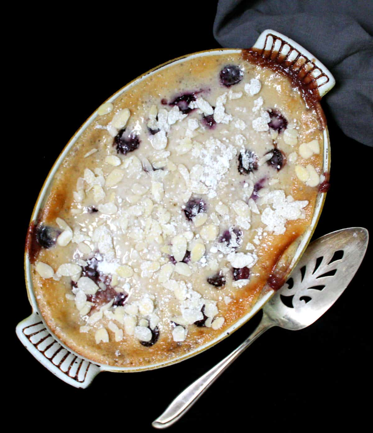 Overhead shot of vegan cherry clafoutis in an old fashioned yellow and white baking dish with a pie server and gray napkin.