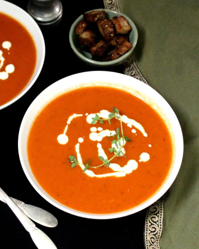 A front/overhead shot of two bowls of vegan tomato soup with whole wheat croutons.