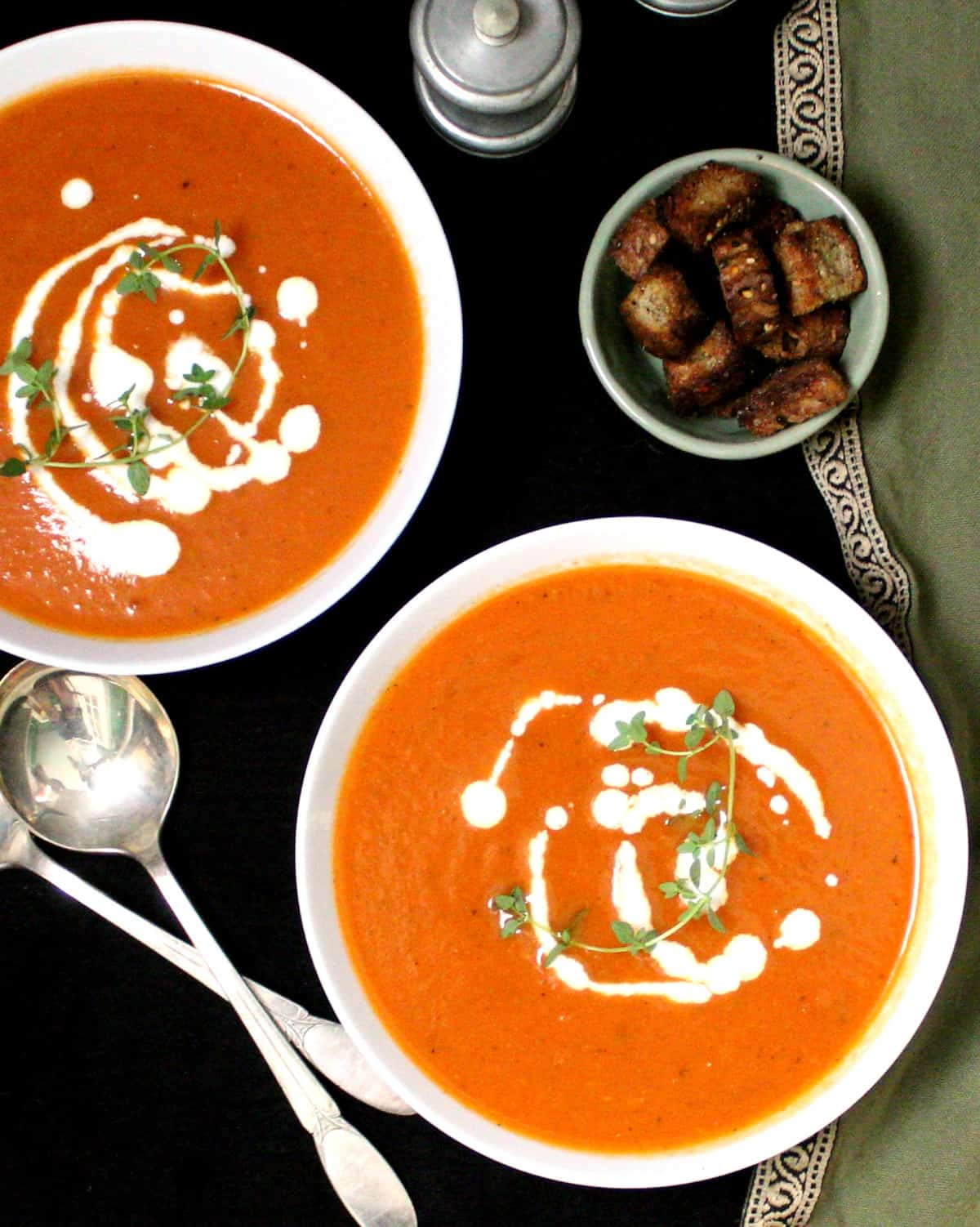 An overhead shot of two bowls of dairyfree vegan tomato soup with thyme, cashew cream, croutons and silver spoons.