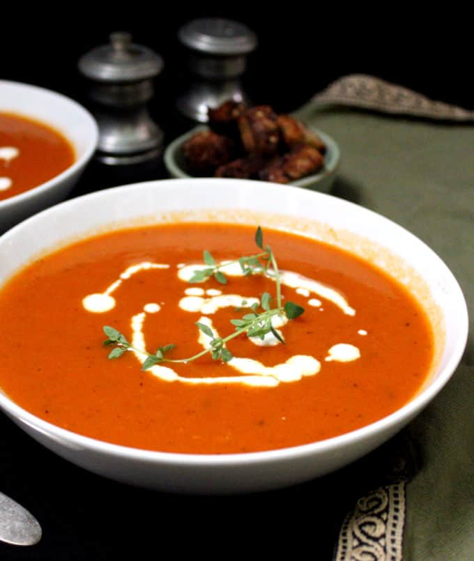 A front partial shot of a bowl of bright red tomato soup with sprigs of thyme, cashew cream and croutons on the side, and salt and pepper shakers and a green napkin beside.