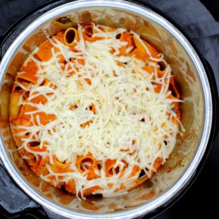 An overhead shot of a black bowl with a serving of creamy, cheesy vegan pasta bake with rigatoni, shreds of vegan mozzarella cheese and a gray napkin.