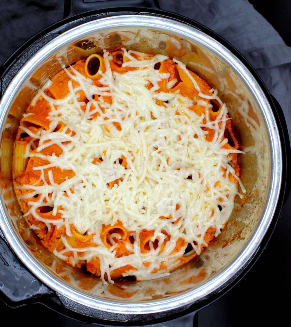 An overhead shot of an Instant Pot with a creamy, cheesy vegan pasta bake with rigatoni, shreds of vegan mozzarella cheese and a gray napkin.