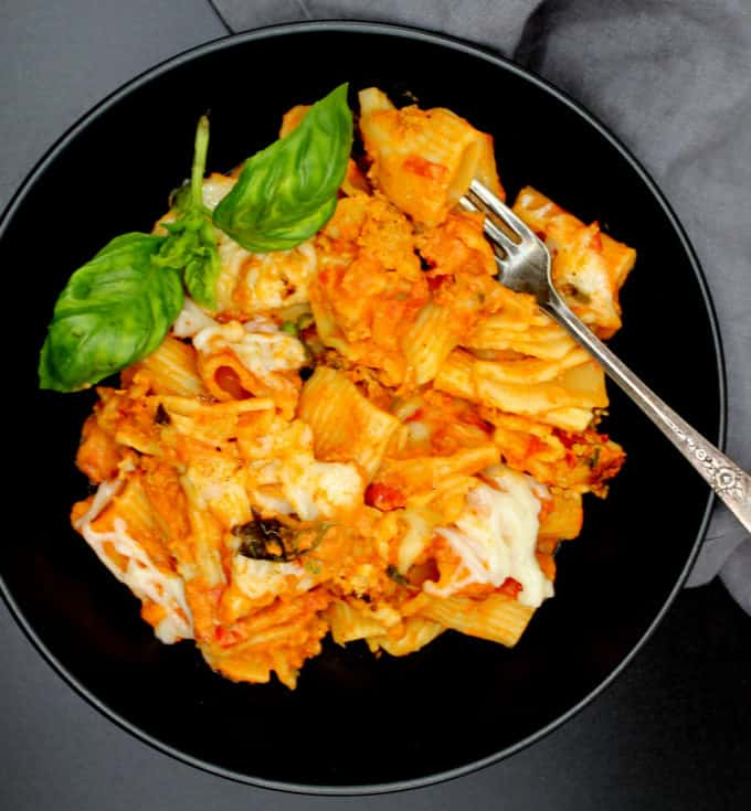 An overhead close shot of a black bowl with a serving of creamy, cheesy vegan pasta bake with rigatoni, shreds of vegan mozzarella cheese and a gray napkin with a silver, decorative fork.