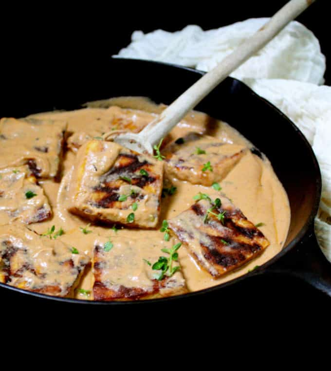 Front shot of grilled tofu steaks with a crosshatch pattern in a creamy orange Cajun sauce in a black cast iron skillet with a ladle and  a cheesecloth in background.