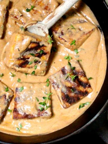 Overhead closeup of grilled tofu steaks in a creamy vegan Cajun sauce in a cast iron skillet with a wooden ladle and cheesecloth
