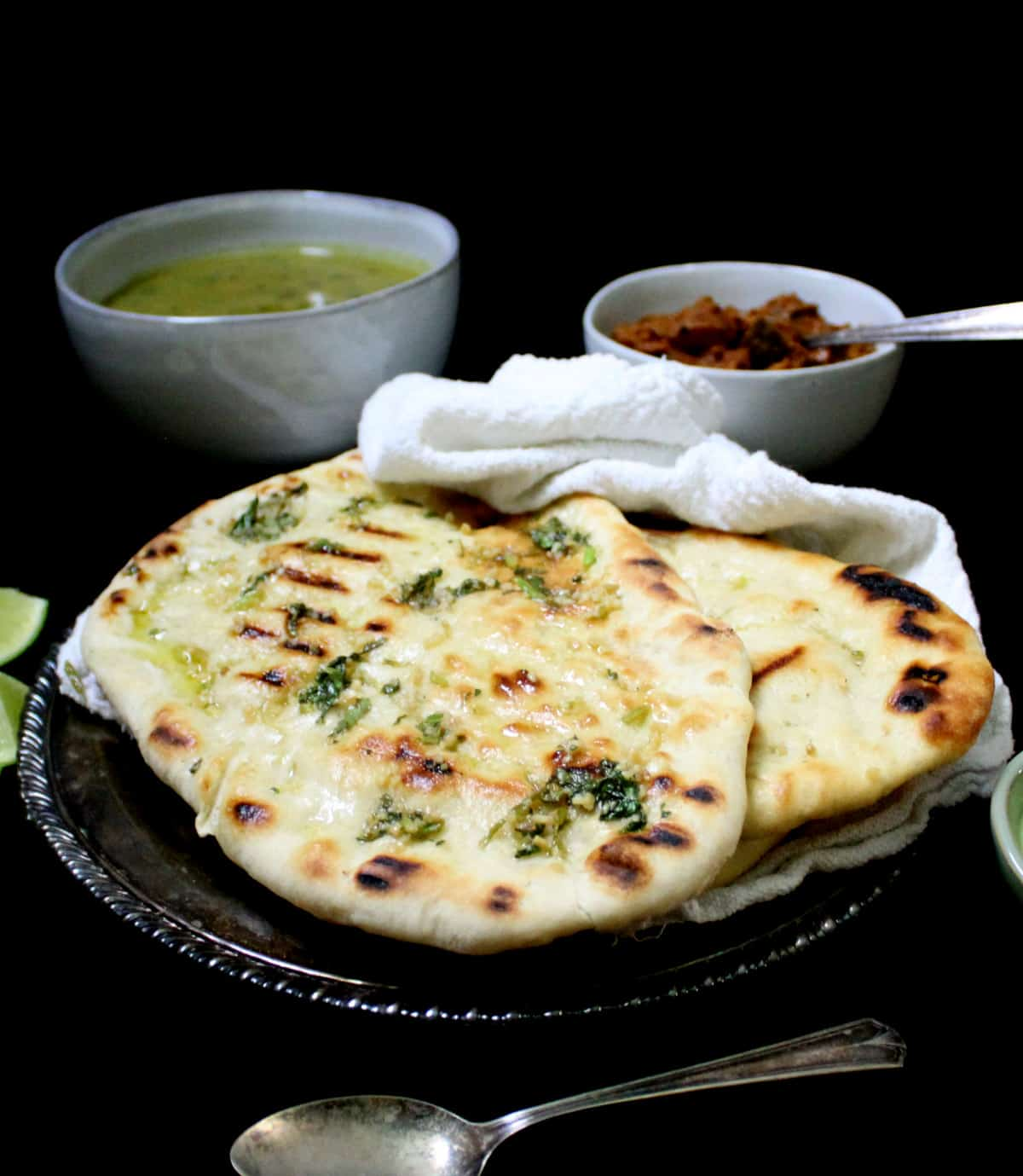 Front shot of a few grilled vegan naan breads in a silver plate with a white napkin and a dal and vegan keema masala on the side with chutney and lemons.