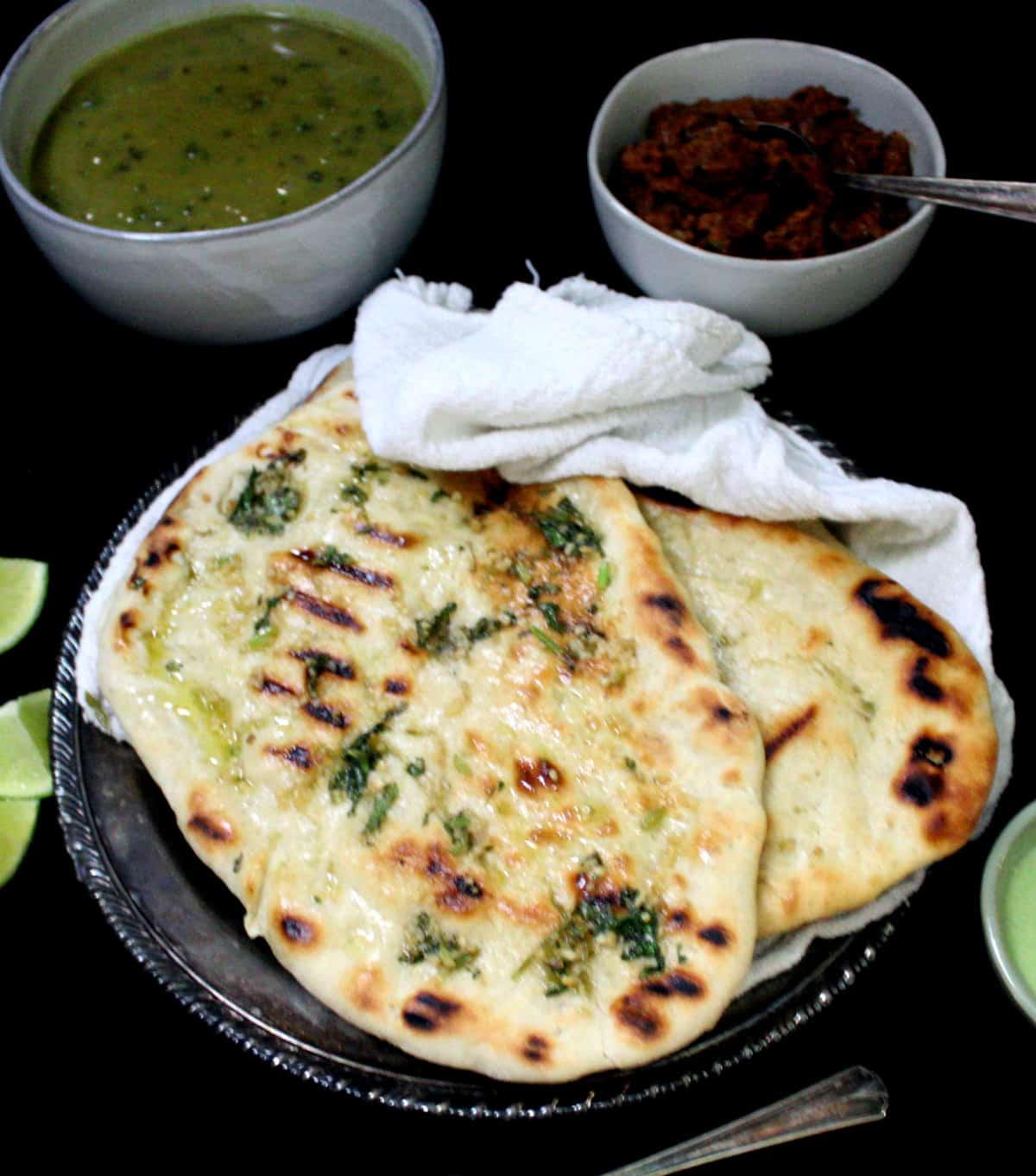 Overhead shot of a few grilled vegan naan breads in a silver plate with a white napkin and a dal and vegan keema masala on the side with chutney and lemons.