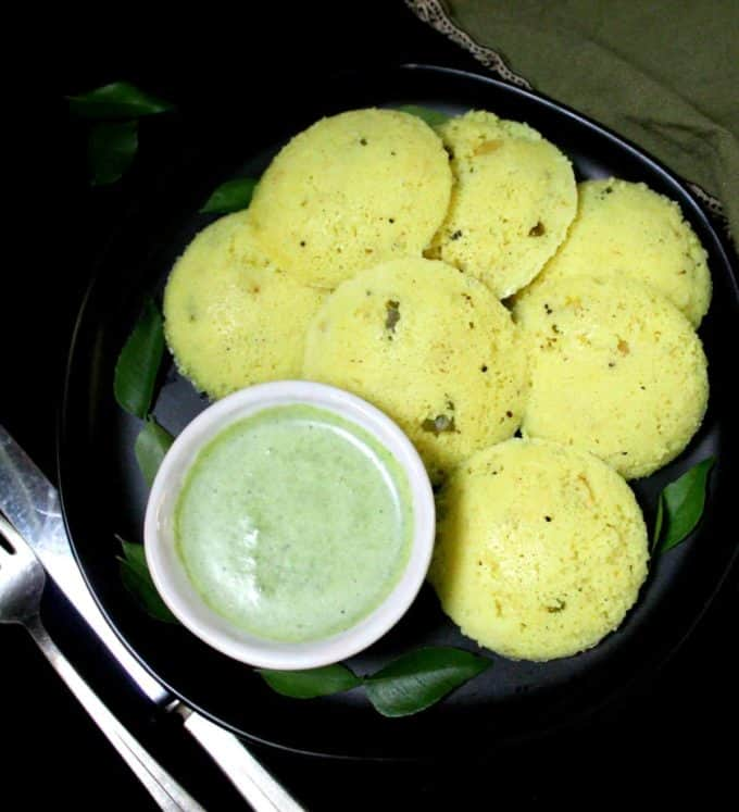 Overhead shot of black plate with fluffy, spongy south Indian rava idlis with turmeric and a green cilantro coconut chutney.