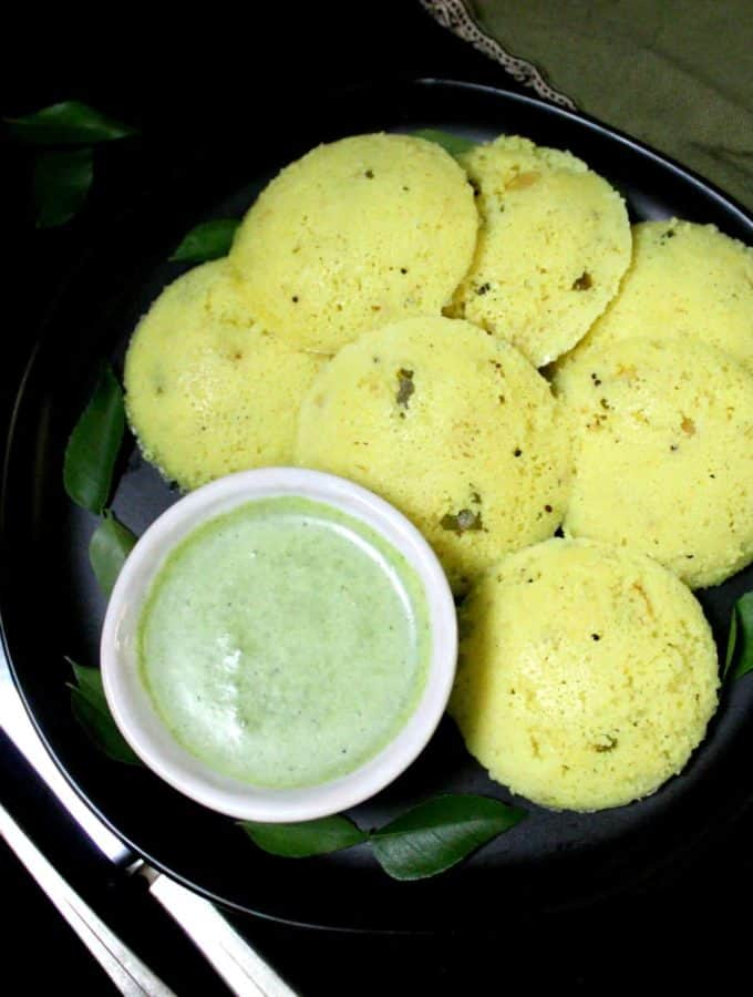 Yellow rava idlis made with vegan yogurt on a black plate with cilantro coconut chutney and a knife and fork